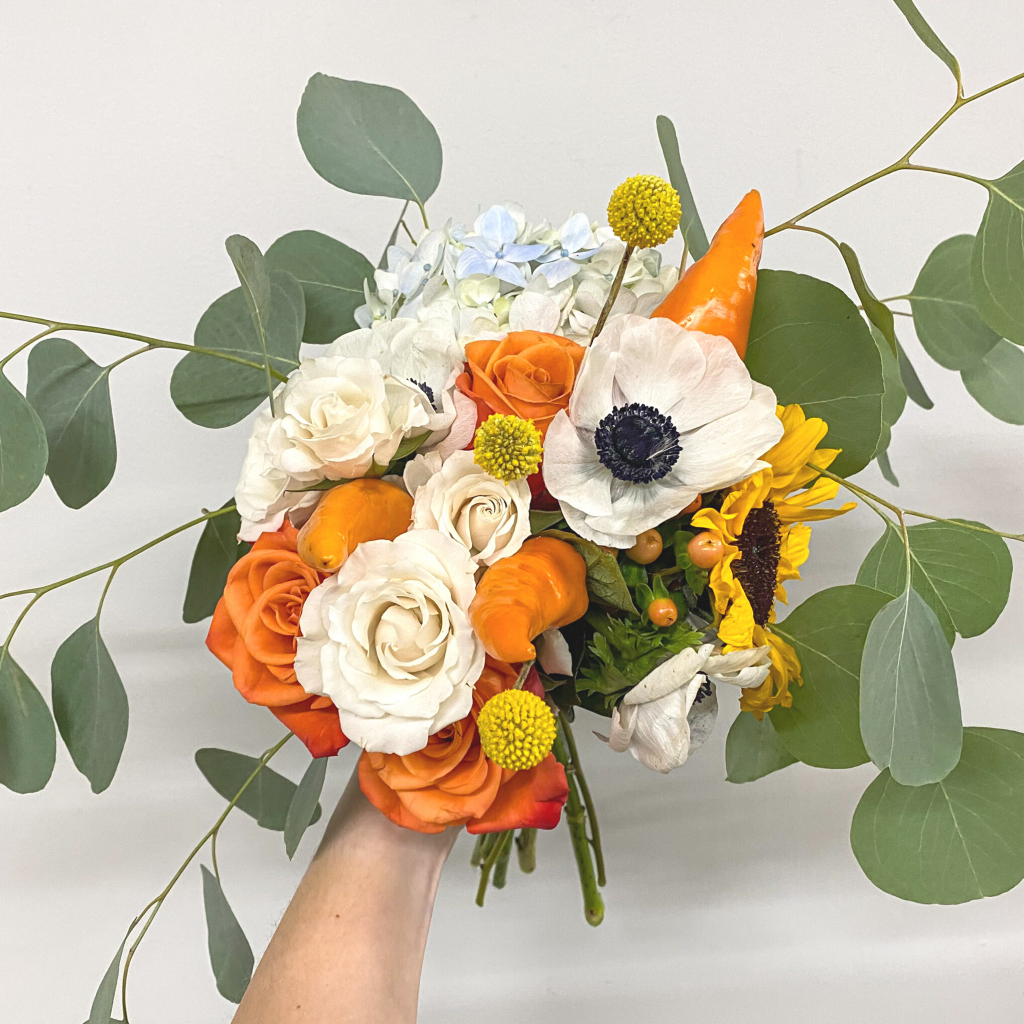 Bouquet of white flowers, orange flowers, and green leaves